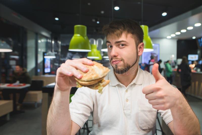 Um homem com um hamburguer em suas mãos senta-se em um restaurante de comida rápida e mostra-se os polegares acima Um homem gosta foto de stock royalty free