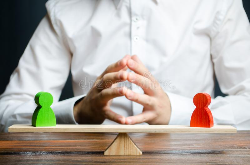 Um homem com mãos no fechamento e olhares nas figuras vermelhas e verdes rivais no escalas O conceito da resolução do conflito imagens de stock royalty free