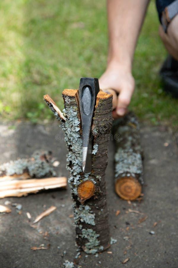 Um homem com um machado que desbasta logs Machado no calço de madeira imagens de stock royalty free