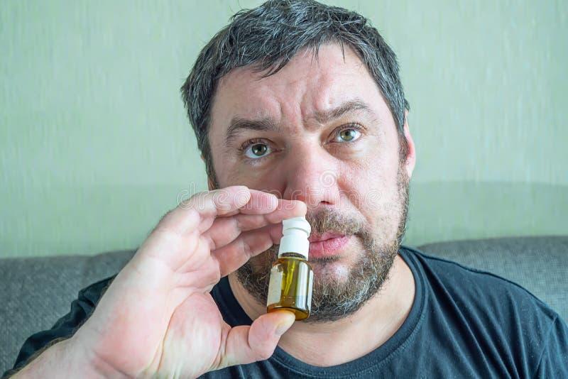 Um homem com um nariz frio cura fotografia de stock