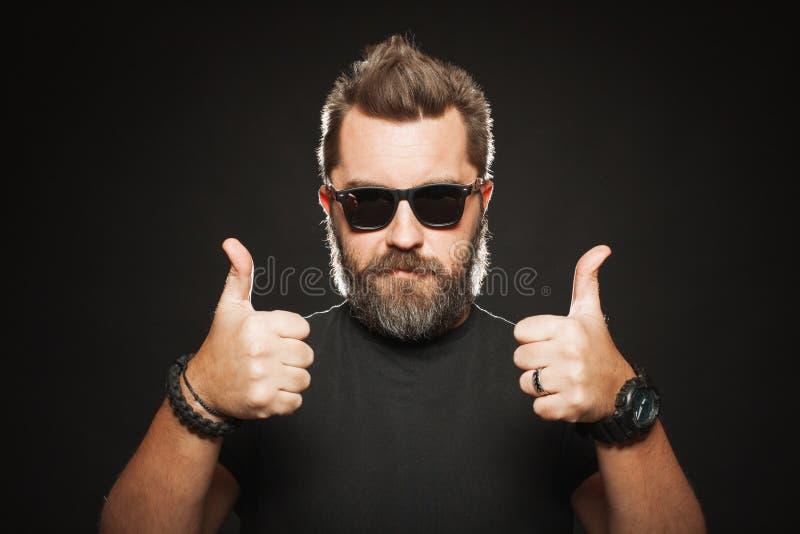 Um homem com um penteado à moda e uma barba consideráveis, fortes mostram dois polegares acima no estúdio em um fundo preto Com e imagens de stock