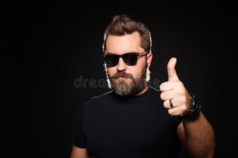 Um homem com um penteado à moda e uma barba consideráveis, fortes mostram o polegar acima no estúdio em um fundo preto com espaço fotos de stock royalty free