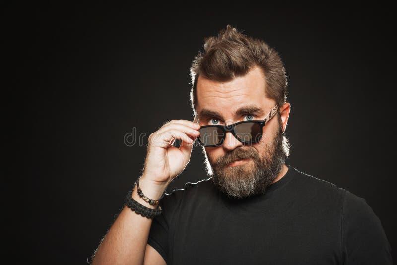 Um homem com um penteado à moda e uma barba consideráveis, fortes vestem óculos de sol e sorrisos no estúdio em um fundo preto co fotografia de stock royalty free