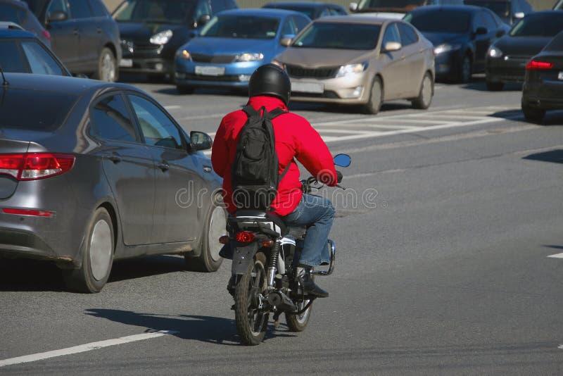 Um homem com um revestimento vermelho e uma trouxa preta que montam uma bicicleta motorizada imagem de stock royalty free