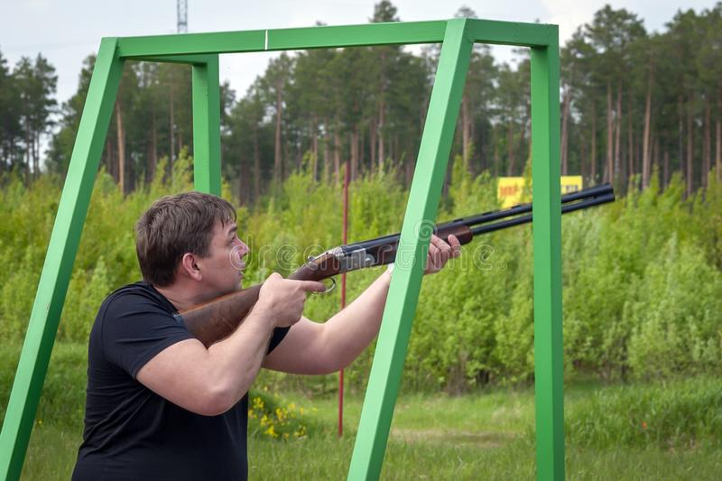 Um homem com um rifle dos esportes na escala de tiro imagens de stock royalty free