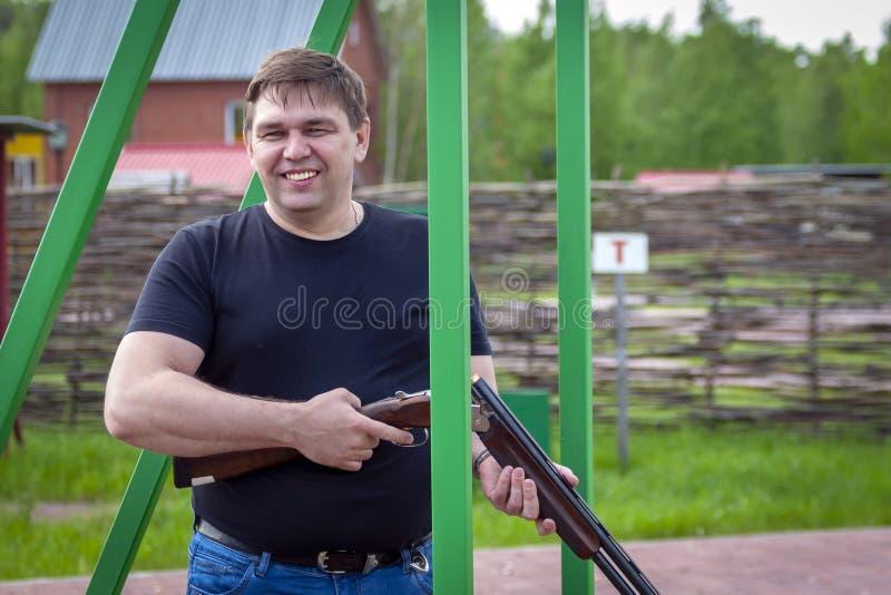 Um homem com um rifle dos esportes na escala de tiro imagem de stock royalty free