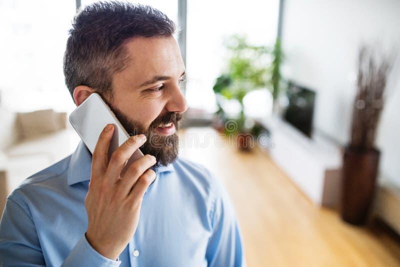Um homem com um smartphone que faz um telefonema em casa imagens de stock