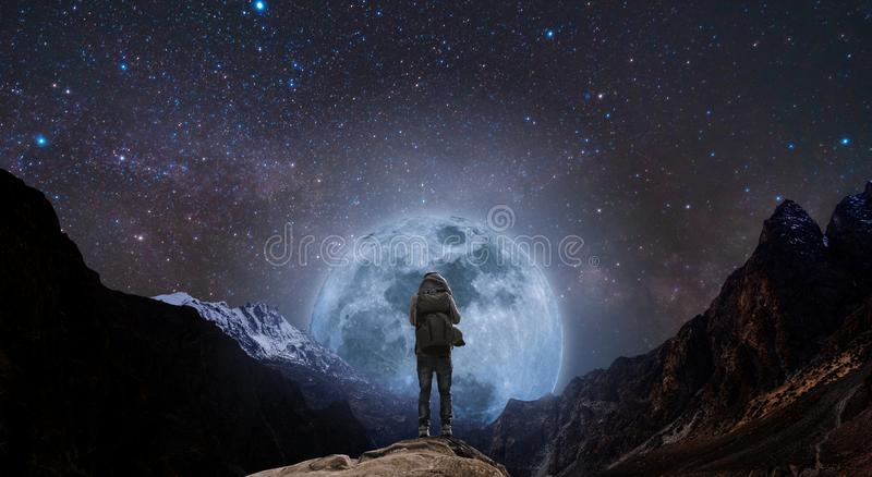 Um homem com a trouxa que está no pico de montanha na noite, e montanha da silhueta com Lua cheia e o céu brilhantes completament fotos de stock royalty free