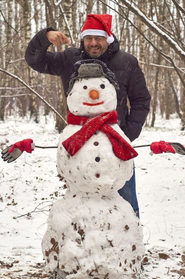Um homem com um boneco de neve foto de stock