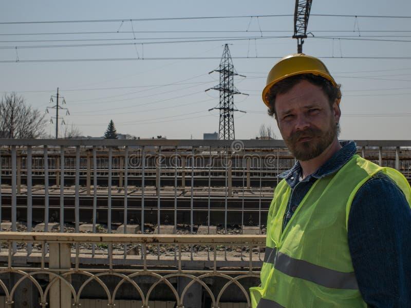 Um homem com uma barba e um bigode em um capacete est? em uma ponte perto das trilhas de estrada de ferro Trabalhador Railway fotos de stock royalty free