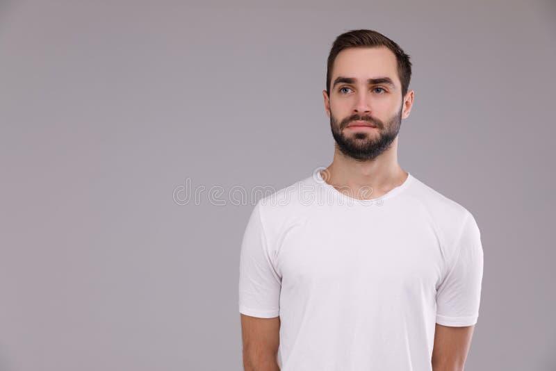 Um homem com uma barba em um t-shirt branco em um fundo cinzento fotografia de stock