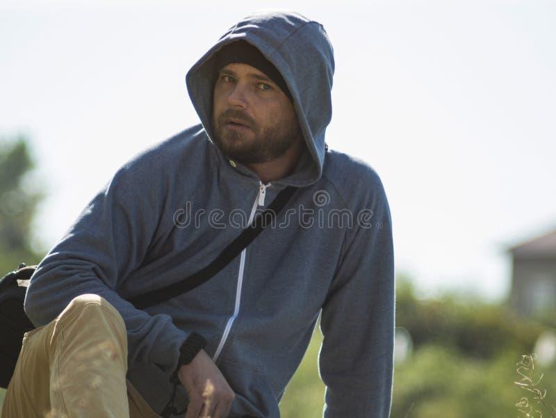 Um homem com uma barba está sentando-se no fundo do céu e na floresta na capa imagens de stock