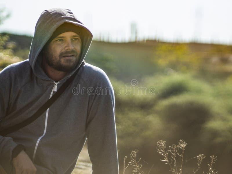 Um homem com uma barba está sentando-se no fundo do céu e na floresta na capa imagens de stock royalty free