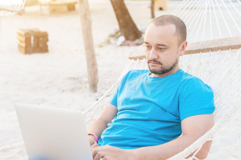 Um homem com uma barba que encontra-se em uma rede com um portátil e em olhares em fotografia de stock