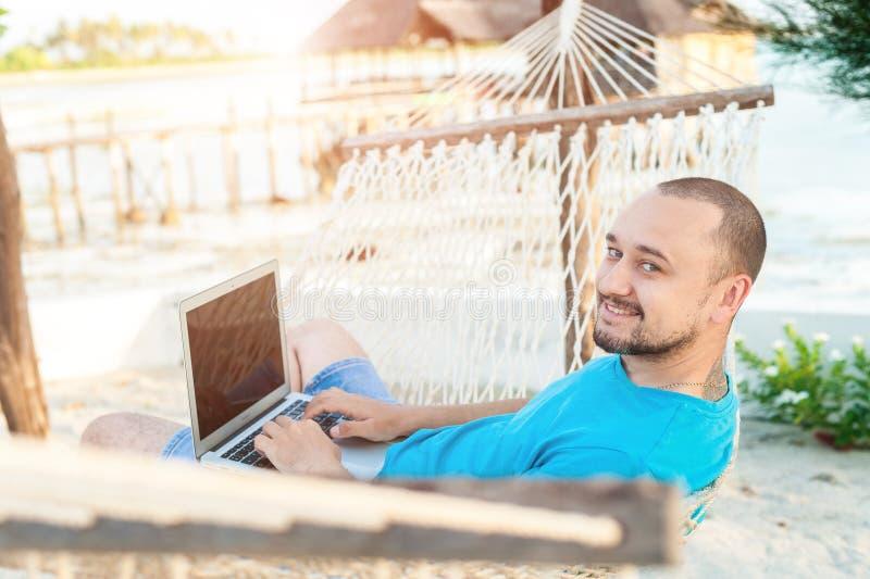 Um homem com uma barba que encontra-se em uma rede com um portátil Trabalho remoto imagens de stock