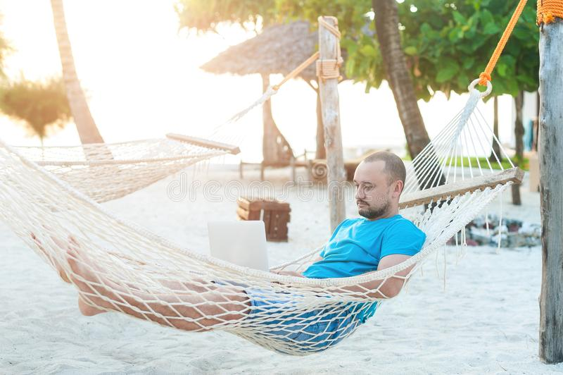 Um homem com uma barba que encontra-se em uma rede com um portátil Trabalho remoto foto de stock royalty free