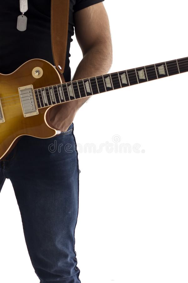 Um homem com uma guitarra elétrica que inclina-se contra uma parede do cimento feliz e relaxado esperando a mostra imagens de stock