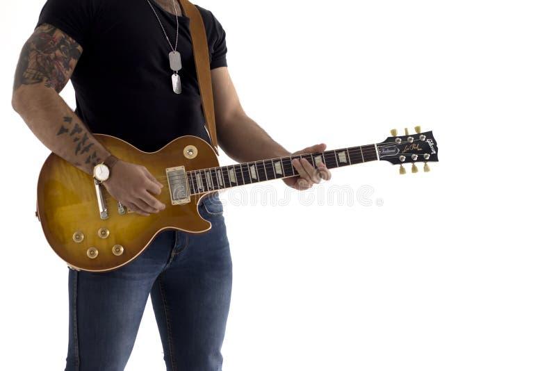 Um homem com uma guitarra elétrica que inclina-se contra uma parede do cimento feliz e relaxado esperando a mostra fotografia de stock royalty free