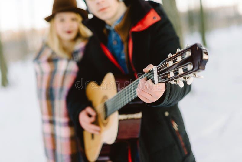 Um homem com uma guitarra, guardando as mãos com seu momento sensual atmosférico da amiga Pares à moda do moderno no olhar na mod imagem de stock royalty free