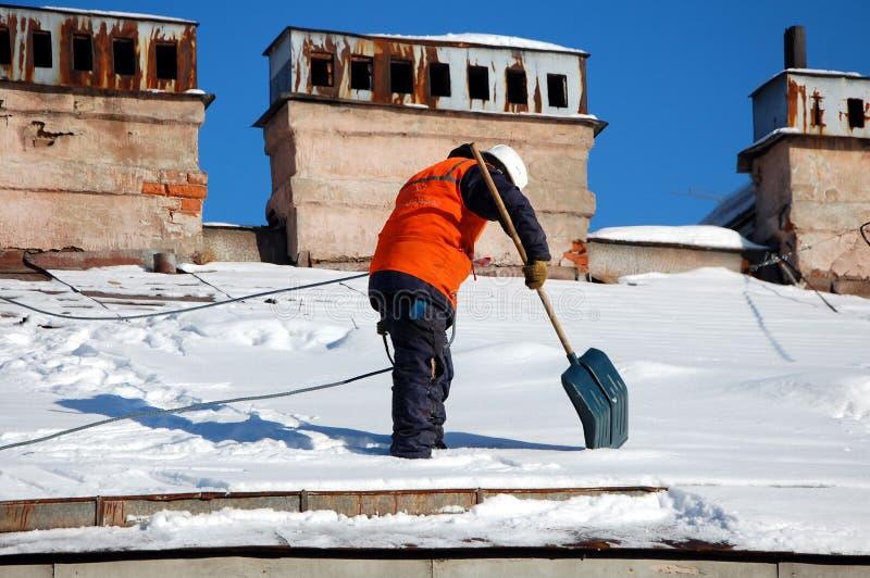 Um homem com uma pá remove a neve de um telhado imagens de stock