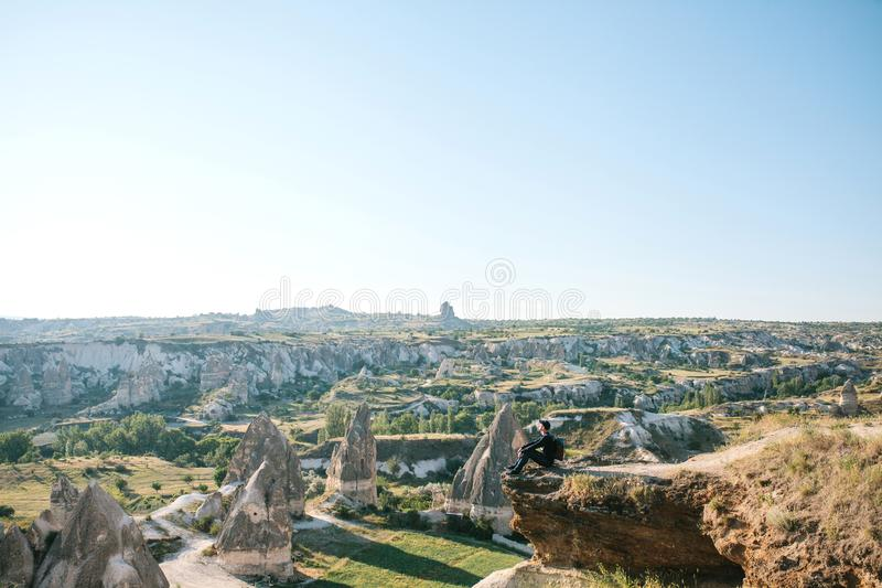 Um homem com uma trouxa senta-se sobre um monte em Cappadocia em Turquia foto de stock royalty free