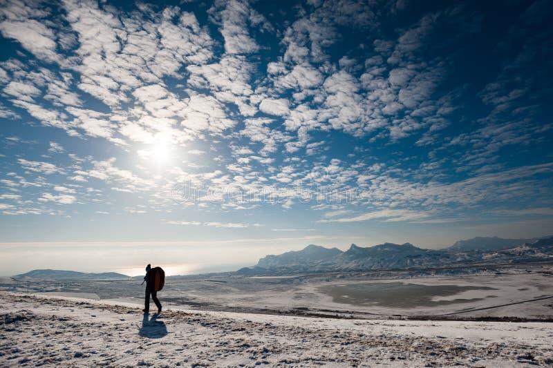 Um homem com uma trouxa vai na neve com montanhas e no mar no fundo imagem de stock royalty free