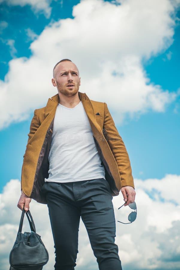 Um homem confiável e atraente à espera do seu transporte usando uma camiseta branca, uma jaqueta castanha e calças confortáveis c imagens de stock
