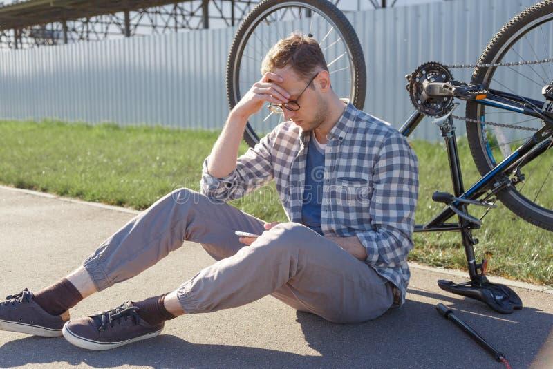 Um homem confundido procura o Internet pela causa de um mau funcionamento da bicicleta ao sentar-se na estrada A bicicleta é gira imagem de stock royalty free