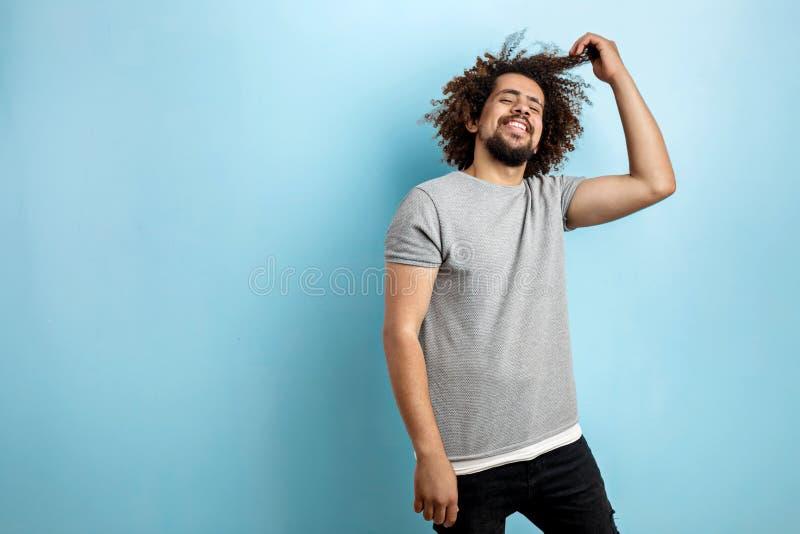 Um homem considerável de cabelo encaracolado que veste um t-shirt cinzento está estando com um sorriso feliz e está tocando em se imagens de stock royalty free