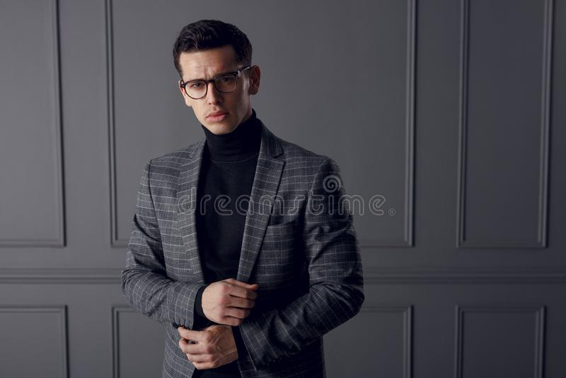 Um homem considerável em um revestimento cinzento e em uma gola alta preta, estando na parte dianteira e olhando seguros, no fund imagens de stock