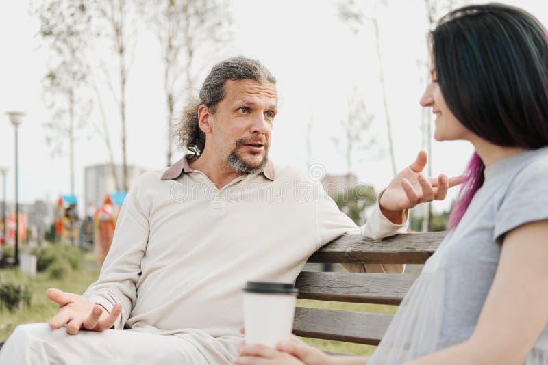 Um homem considerável idoso com cabelo longo na cauda e uma mulher bonita nova estão sentando-se em um banco e em uma conversa de fotos de stock