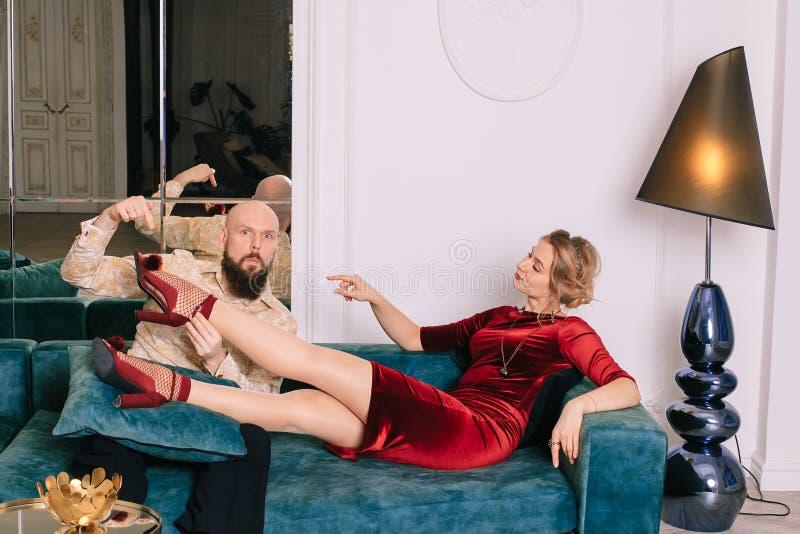 Um homem considerável que beija o pé de uma mulher em sapatas vermelhas imagens de stock royalty free