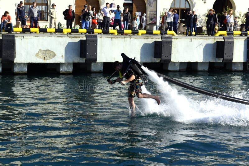 Um homem corre através da água imagens de stock royalty free