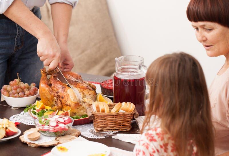 Um homem corta cozeu a Turquia na mesa de jantar imagens de stock royalty free