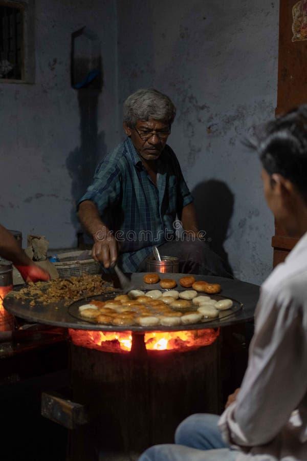 Um homem cozinha acima um alimento popular da rua chamado tikki do aloo fotos de stock