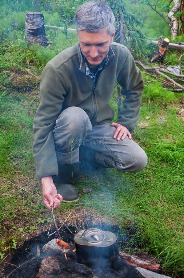 Um homem cozinha salsichas no incêndio fotos de stock