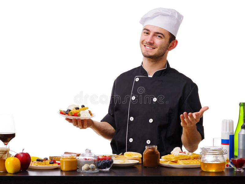 Um homem, um cozinheiro, está na cozinha com uma placa de waffles belgas fotos de stock royalty free