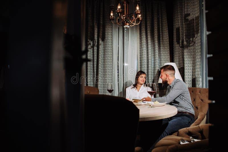 Um homem dá um presente a sua amiga em uma data em um restaurante imagens de stock royalty free