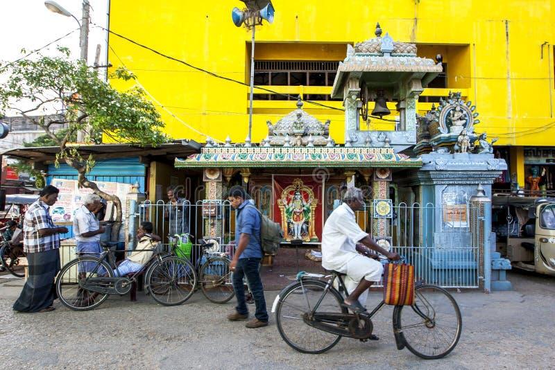 Um homem dá um ciclo após um templo hindu pequeno ao lado da estação de ônibus de Jaffna em Sri Lanka imagem de stock