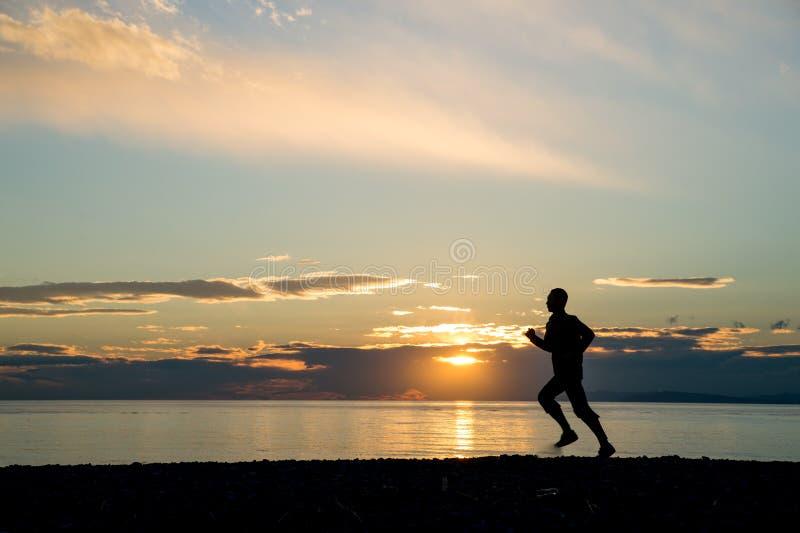 Um homem de corrida na praia imagens de stock