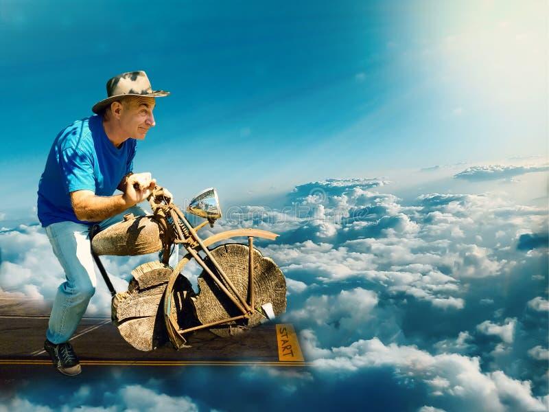 Um homem de envelhecimento em uma motocicleta de madeira decola da pista de decolagem no céu para o sol fotografia de stock royalty free