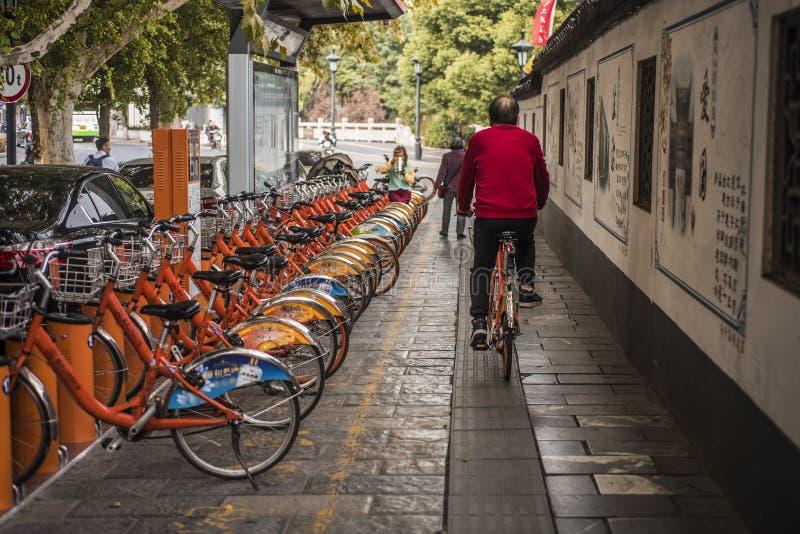 Um homem de meia idade em uma camisa vermelha monta uma bicicleta compartilhada através de um ponto de estacionamento compartilha imagens de stock royalty free
