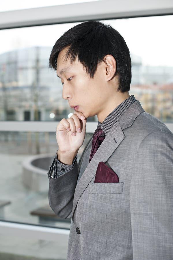 Um homem de negócio chinês pensativo foto de stock