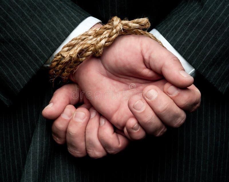 Um homem de negócio com suas mãos amarradas atrás da parte traseira do HS fotos de stock royalty free