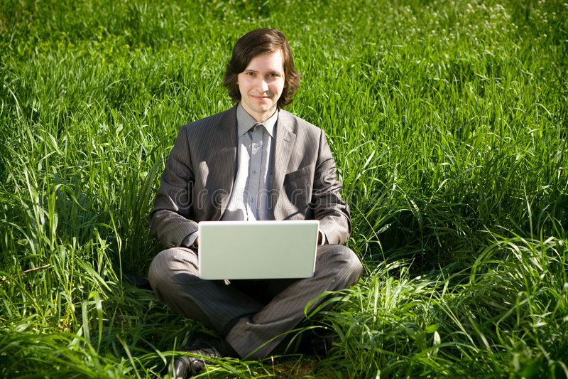 Um homem de negócio com um portátil no campo de grama imagens de stock royalty free