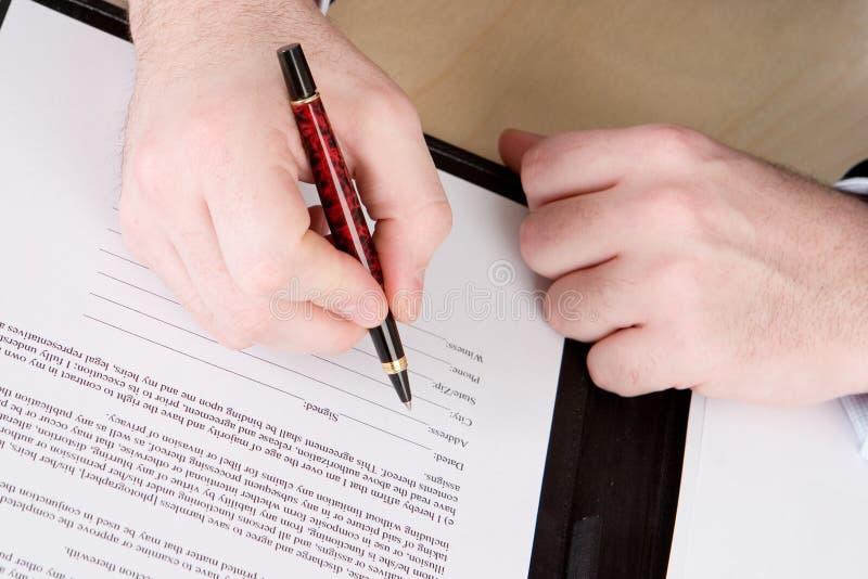 Um homem de negócio com uma pena vermelha e preta aproximadamente para assinar um original imagem de stock royalty free