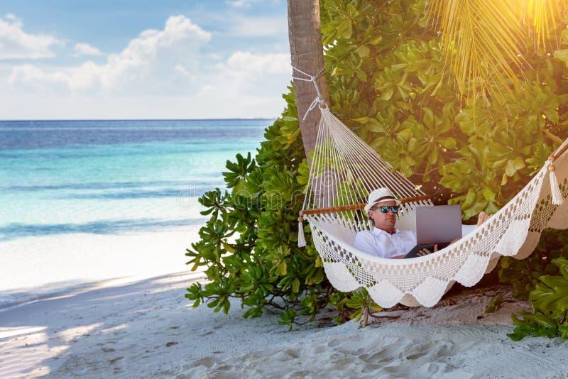 Um homem de neg?cio em trabalhos das f?rias em seu port?til em uma praia tropical fotografia de stock