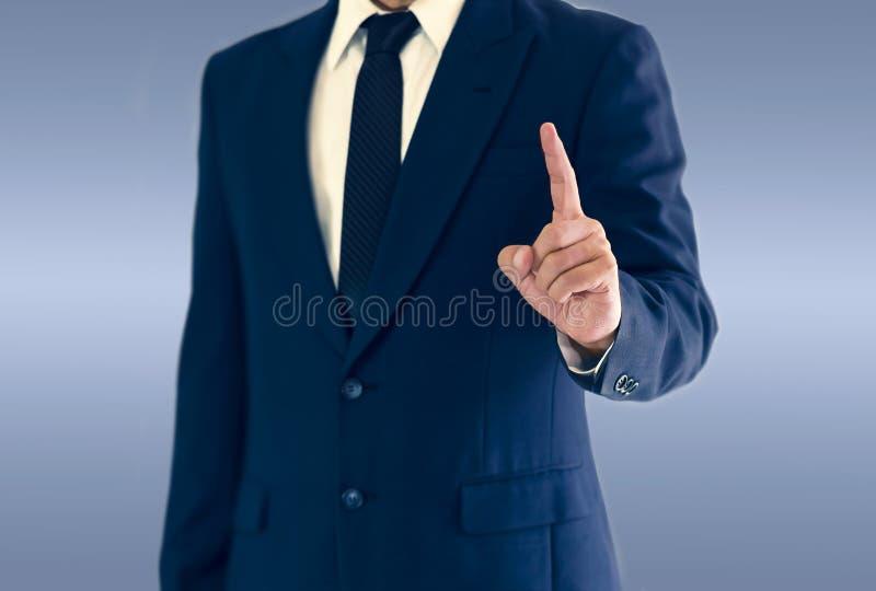 Um homem de negócios é estando e apontando a mão fotos de stock royalty free