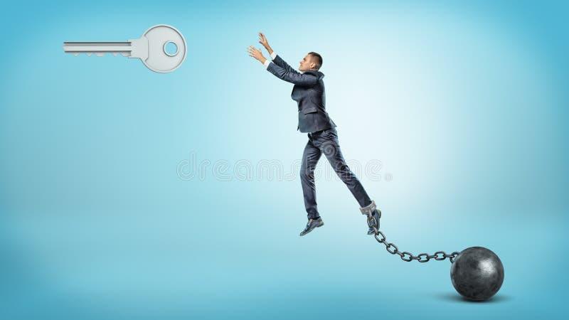 Um homem de negócios acorrentado a uma bola do ferro tenta saltar e alcançar uma grande chave de prata que pendura acima imagens de stock
