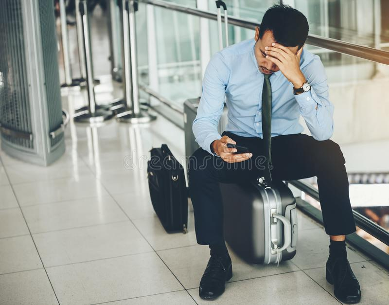 Um homem de negócios asiático está sentando-se em sua bagagem Foi forçado fotografia de stock royalty free